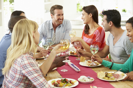 male friends: Group Of Friends Making Toast Around Table At Dinner Party