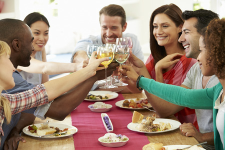 tomando vino: Grupo de amigos que hacen la tostada alrededor de la mesa en la cena de la fiesta