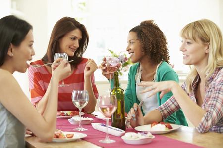 woman in white: Group Of Women Sitting Around Table Eating Dessert Stock Photo