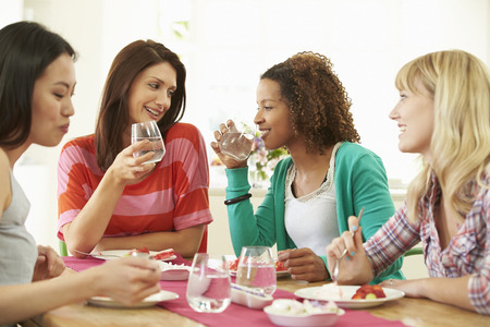 Group Of Women Sitting Around Table Eating Dessert Stockfoto