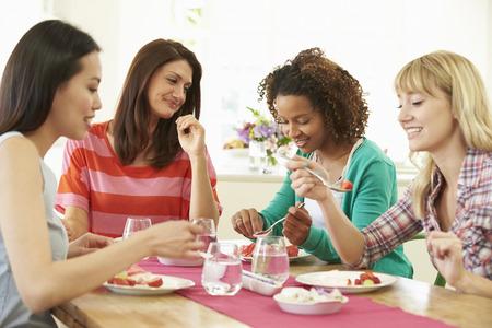 デザートを食べるテーブルの周りに座っての女性のグループ