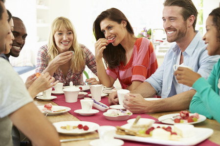 party table: Group Of Friends Having Cheese And Coffee Dinner Party Stock Photo