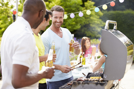 Group Of Men Cooking On Barbeque At Home photo