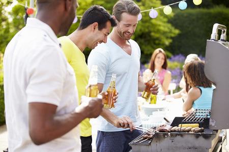 Gruppe von Männern das Kochen auf Grill At Home