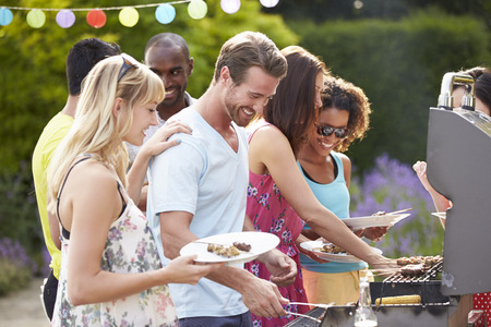 food buffet: Group Of Friends Having Outdoor Barbeque At Home Stock Photo