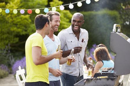 tomando alcohol: Grupo de hombres que cocinan en la barbacoa en casa