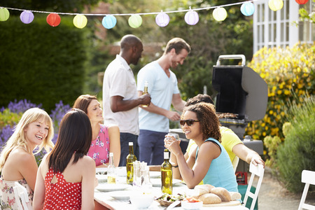 party food: Group Of Friends Having Outdoor Barbeque At Home Stock Photo