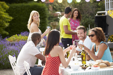 party with food: Group Of Friends Having Outdoor Barbeque At Home Stock Photo