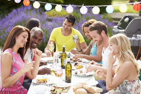 garden barbecue: Group Of Friends Having Outdoor Barbeque At Home Stock Photo
