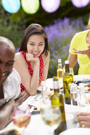 Young Woman Relaxing At Outdoor Barbeque photo