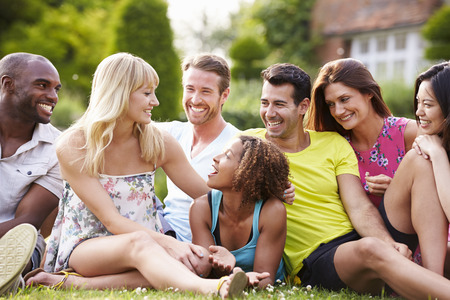 Group Of Friends Sitting On Grass Together photo