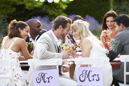 신부와 신랑은 결혼식 피로연에서 식사를 즐기는