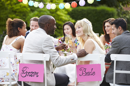 Bride And Groom Enjoying Meal At Wedding Reception photo