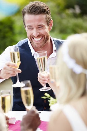 reception desk: Friends Proposing Champagne Toast At Wedding
