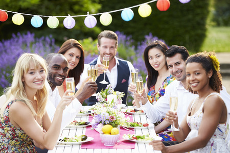 party with food: Group Of Friends Enjoying Outdoor Dinner Party Stock Photo
