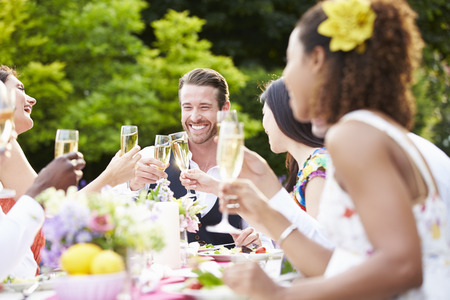 proposing a toast: Group Of Friends Enjoying Outdoor Dinner Party Stock Photo