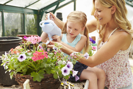 Mother And Daughter Watering Plants In Greenhouse