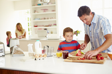 jam: Son Helping Father To Prepare Family Breakfast In Kitchen