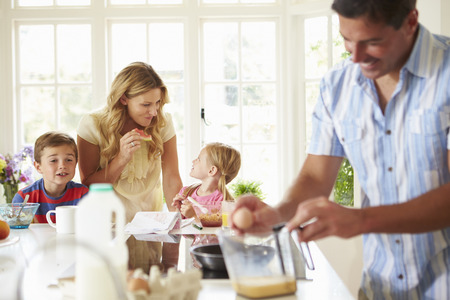 petit dejeuner: P�re pr�parer le petit d�jeuner de la famille en cuisine Banque d'images