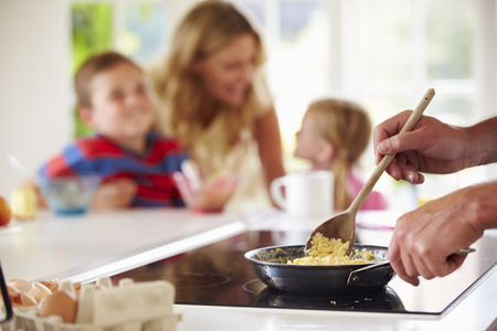 Close Up Of Father Preparing Family Breakfast In Kitchen