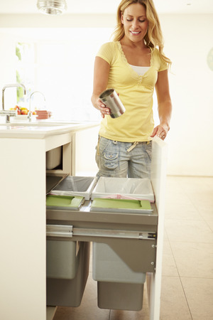 Woman Recycling Kitchen Waste In Bin photo