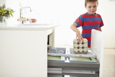 Boy Recycling Kitchen Waste In Bin