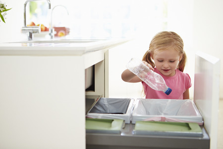 trash can: Girl Recycling Kitchen Waste In Bin Stock Photo