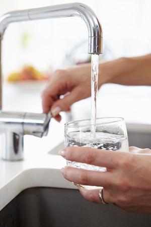 llave de agua: Cerca de la mujer que vierte vaso de agua de grifo en la cocina