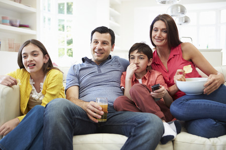 sofa television: Hispanic Family Sitting On Sofa Watching TV Together Stock Photo