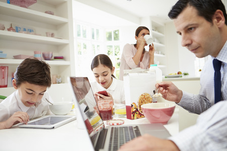 Family Using Digital Devices At Breakfast Table Standard-Bild