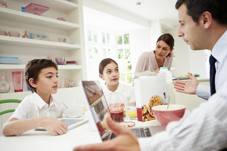 Family Using Digital Devices Having Argument Over Breakfast photo