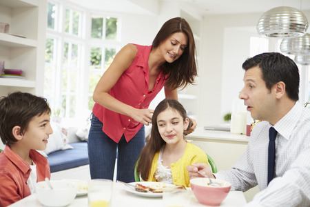 Family Having Breakfast Before Husband Goes To Work photo
