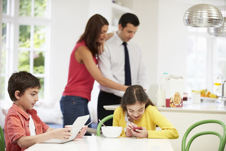 Family Using Digital Devices At Breakfast Table photo