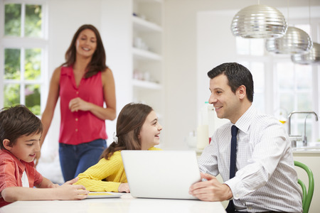 family kitchen: Family Using Digital Devices At Breakfast Table Stock Photo