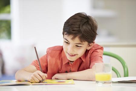キッチンで宿題をしているヒスパニック系の少年