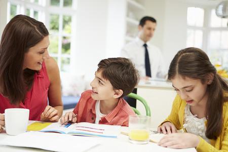 niños estudiando: Mamá ayuda a niños con la tarea Cuando papá trabaja en segundo plano Foto de archivo