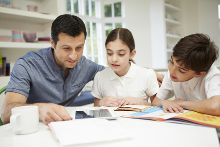 helping children: Father Helping Children With Homework Using Digital Tablet Stock Photo