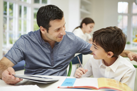 Father Helping Son With Homework Using Digital Tablet Stock Photo