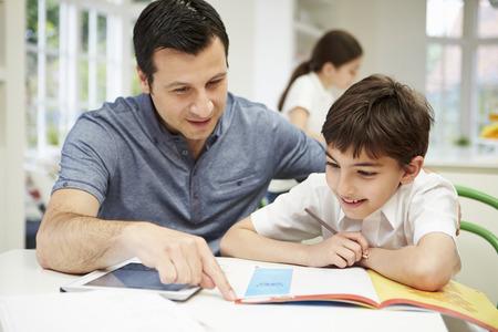 niños leyendo: Hijo de ayuda del padre con la preparación que usa la tablilla digital