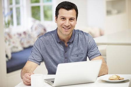 Hispanic Man Using Laptop In Kitchen At Home photo