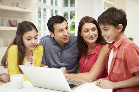 Family Looking at Laptop Over Breakfast Stock Photo