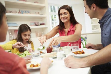 comiendo: Familia hispana sentado en la mesa comiendo comida junto Foto de archivo
