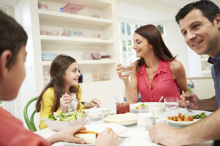 Hispanic Family Sitting At Table Eating Meal Together photo