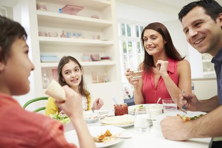 Familia hispana sentado en la mesa comiendo comida junto Foto de archivo