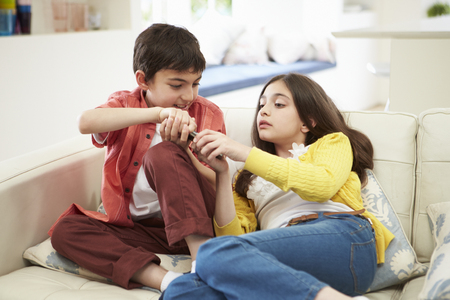 Two Hispanic Children Arguing Over TV Remote Control photo