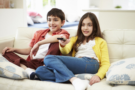 Two Hispanic Children Sitting On Sofa Watching TV Together Archivio Fotografico