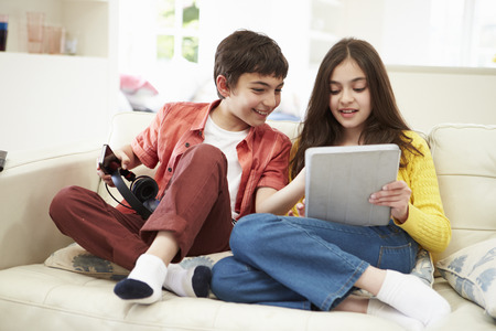 11 year old girl: Children Playing With Digital Tablet And MP3 Player Stock Photo