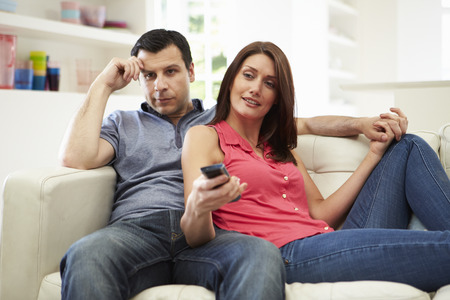 Hispanic Couple Sitting On Sofa Watching TV Together