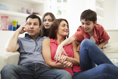 Hispanic Family Sitting On Sofa Watching TV Together photo
