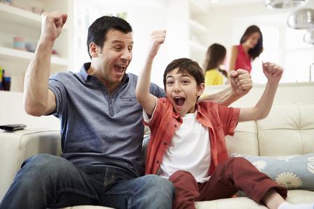 excitación: Padre e hijo mirando deportes en la TV